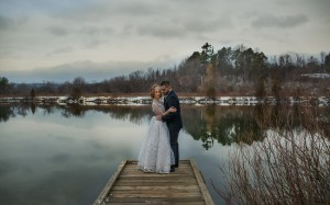 Newlyweds pose on the lake in the Canadian winter.