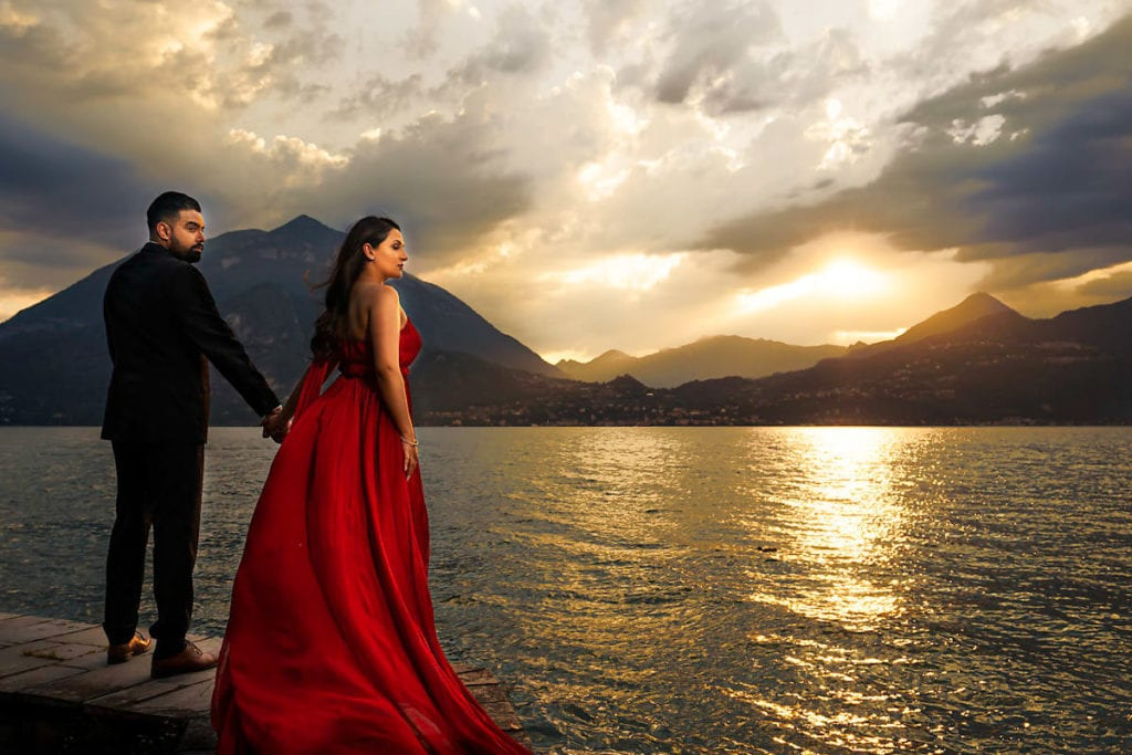 Engagement photo session in Lake Como. Bride in extra long flowy red dress. Sunset, Lake and Italian alps in the background.