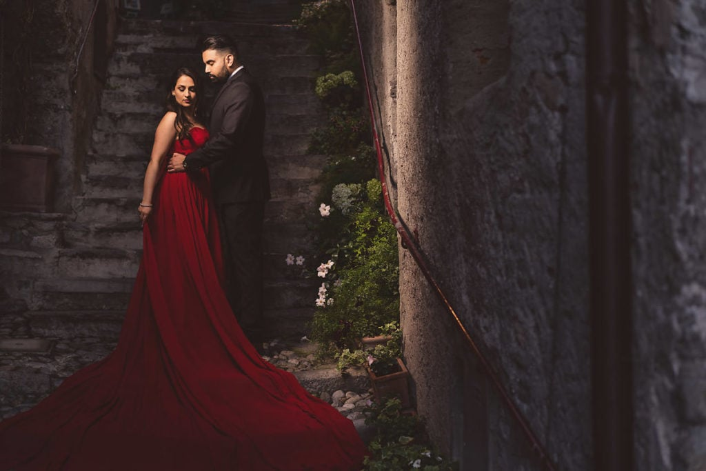 Engagement photo session in Lake Como. Bride in extra long flowy red dress. Rustic staircase behind couple.