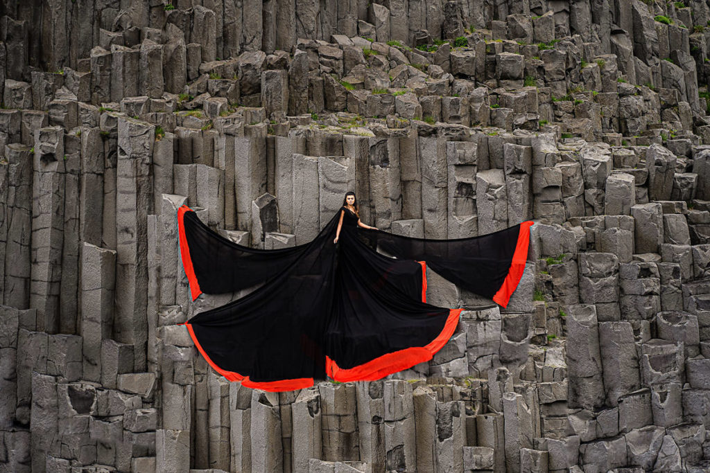 Brede with extra long flowy black with red border dress photoshoot at Black beach with black rocks in Iceland