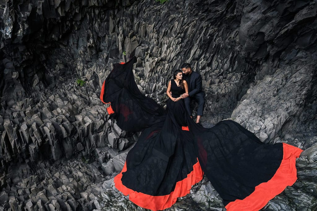Groom and bride with extra long flowy black with red border dress photoshoot at Black beach with black rocks in Iceland