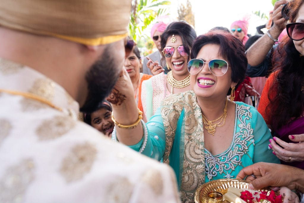 Bride's mother grabs groom nose in traditional Indian way