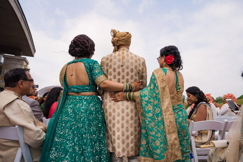 Indian groom walks in towards the outdoor ceremony mandap with mother and sister