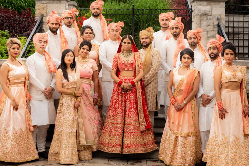 Sabyasachi bride and groom pose with their bridal party at their wedding
