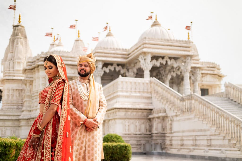 Real Sabyasachi Indian couple pose in front of BAPS mandir Toronto Canada