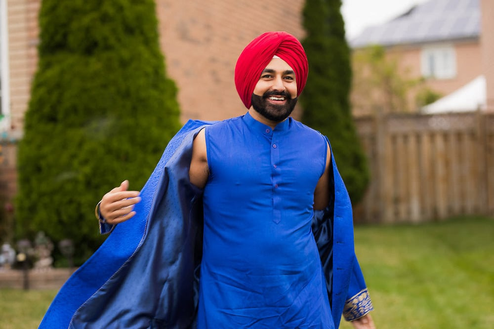 Indian Sikh groom in blue and red outfit getting ready for his Sikh wedding ceremony at Scarborough Gurdwara