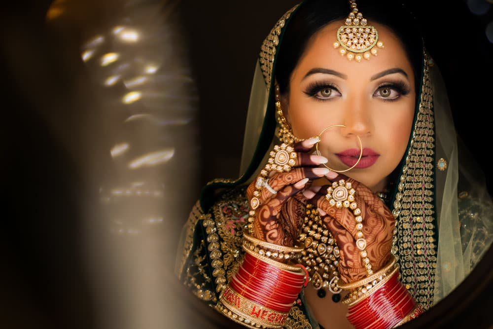 Posing as an Indian Bride. Indian bride in green Sabyasachi Lehenga at her Bollywood-inspired wedding photoshoot.