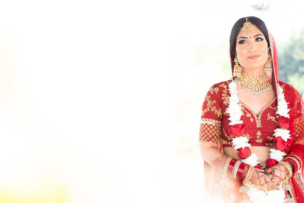 Indian Bride in red lehenga at her Floral Indian Wedding.