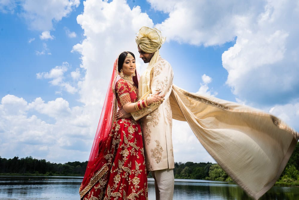 Indian Bride and Groom at their floral Indian wedding with bright blue sky.