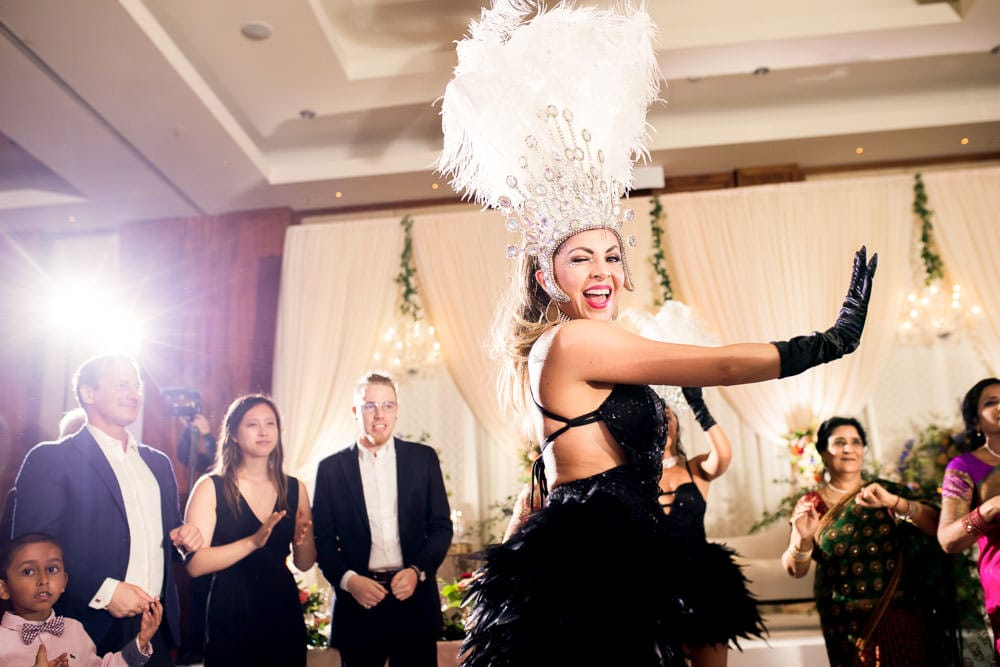 Burlesque dance performance at this floral Indian wedding reception at the Ritz-Carlton Toronto.