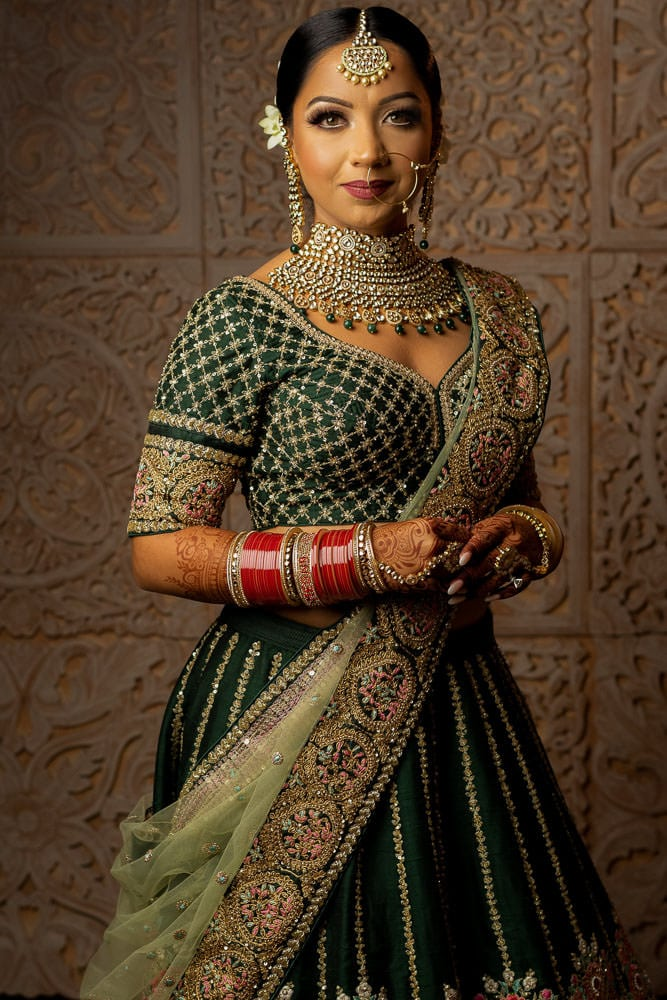 Posing as an Indian bride. Indian bride in green Sabyasachi Lehenga.