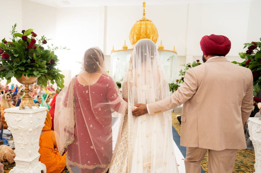 Indian Sikh bride makes her entrance at Anand Karaj with her parents at her side.