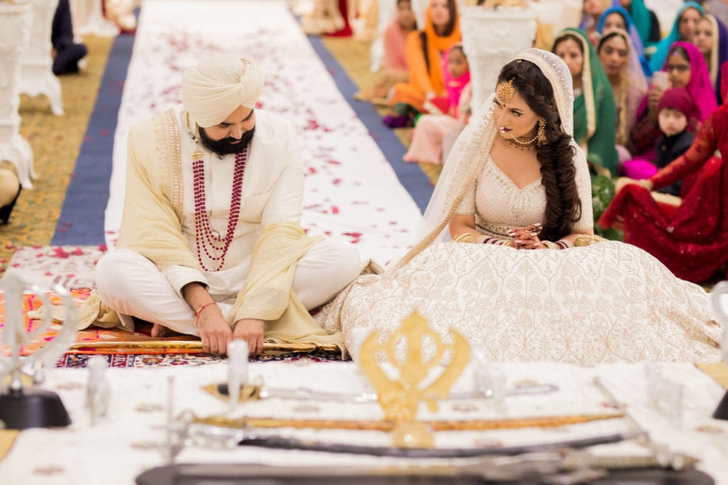 Sikh couple share a sweet smita before the start of their Anand Karaj at Nanaksar Gurdwara in Brampton, Toronto.