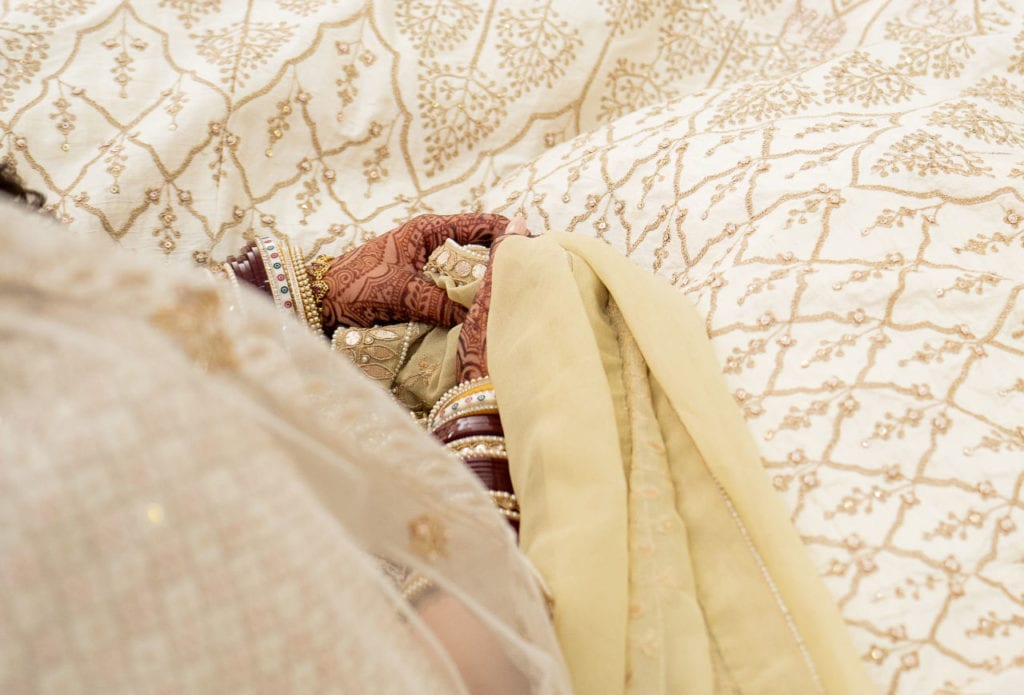 Palla ceremony at Sikh wedding ceremony the Anand Karaj at Nanaksar Gurdwara in Brampton, Toronto. Bride holds onto the palla tightly.