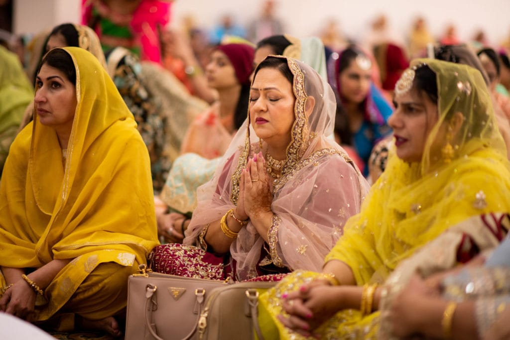 Sikh wedding ceremony the Anand Karaj at Nanaksar Gurdwara in Brampton, Toronto. Mother-of-the-bride holds palms together and prays for the wedding.