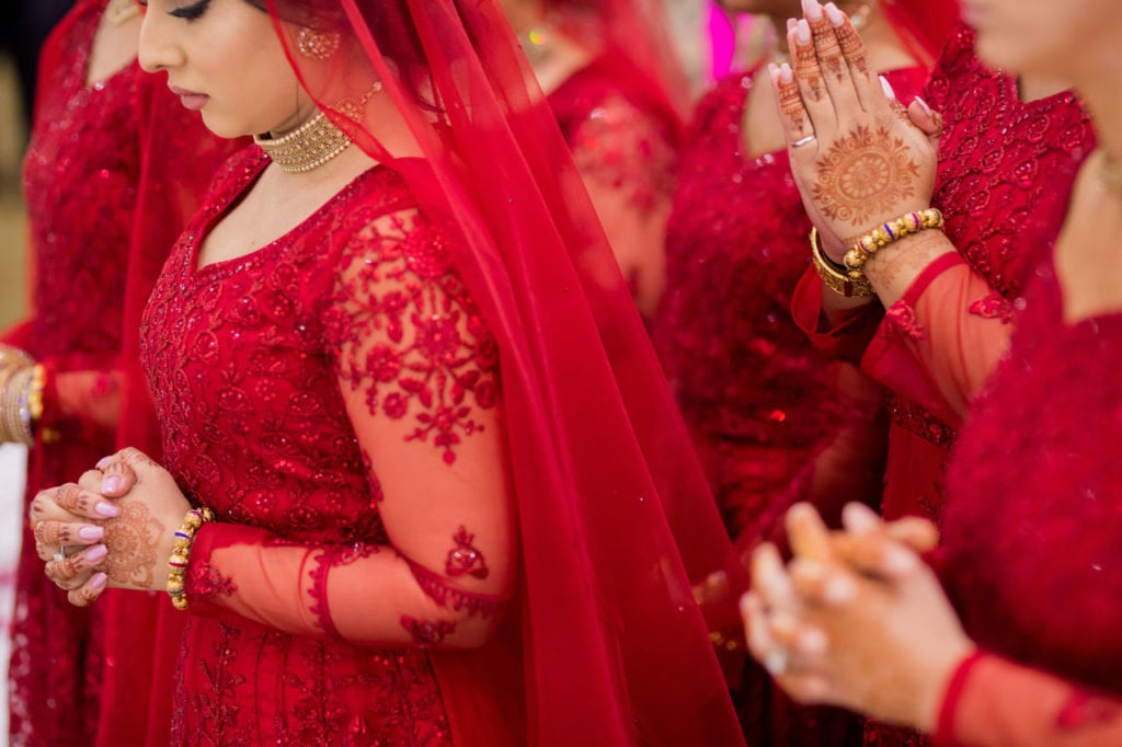 Indian bridesmaids in long deep red gowns dresses.