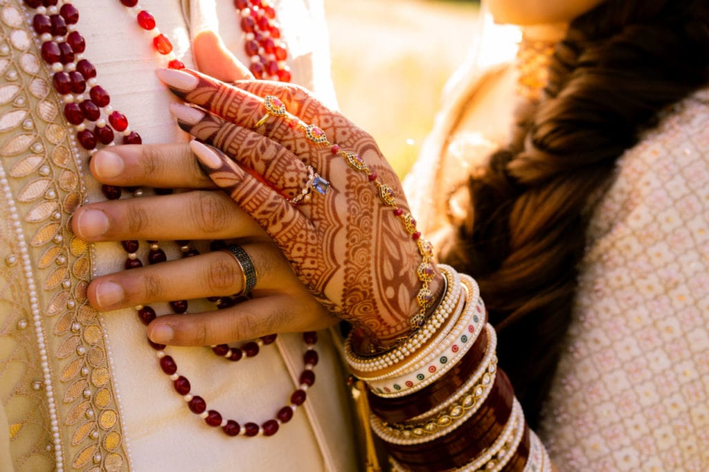 Anita Dongre bride and groom in off-white Indian outfits hold their hands.